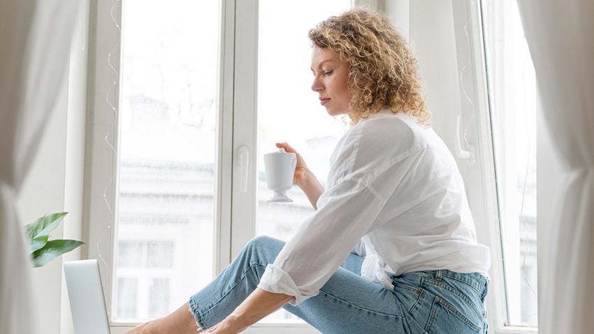Femme blonde assise devant sa fenêtre avec une tasse de café à la main